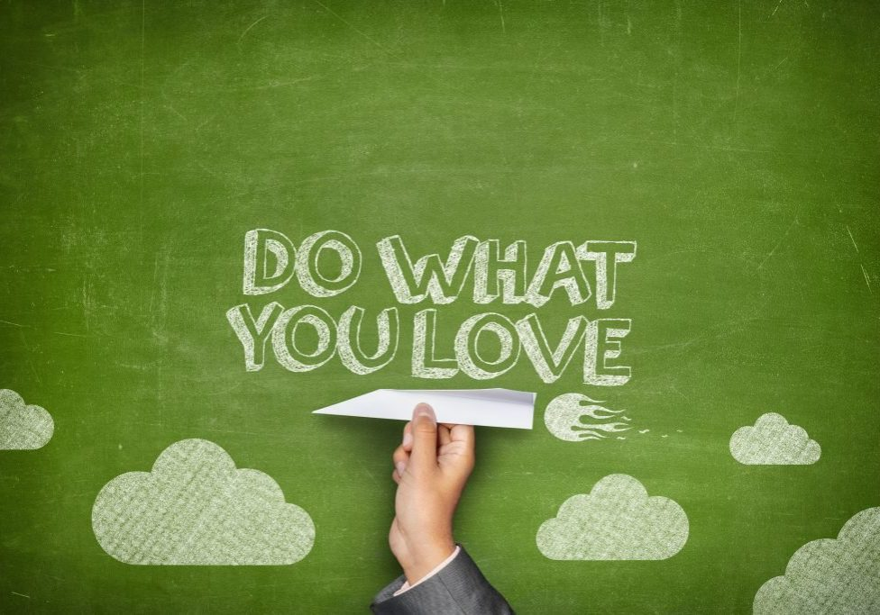 Do what you love concept on green blackboard with businessman hand holding paper plane